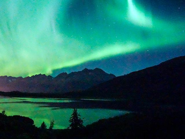 green aurora borealis cloud over mountains reflecting off Robe Lake