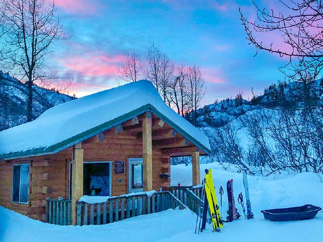 skiing from backcountry cabin with DPS skis and Black Diamond skis during sunset