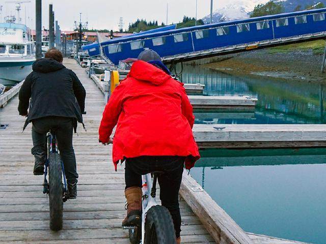 startup employees riding fat bikes on dock of Valdez boat marina