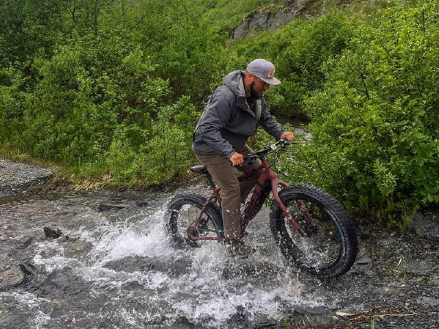 web developer on vacation riding fatbike through river in Alaska