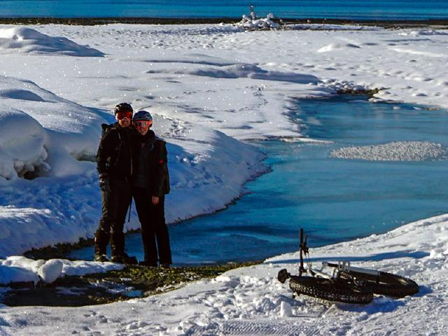 boyfriend and girlfriend smile for photograph during fatbiking trip along Mineral Creek to Prince William Sound