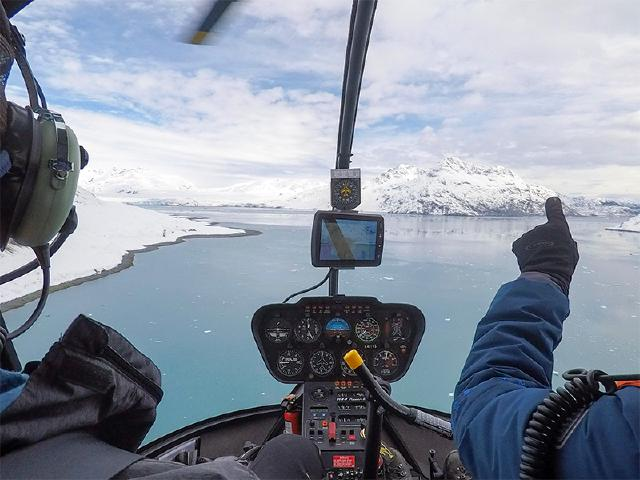 with helicopter pilot pointing to Columbia Glacier on guided tour
