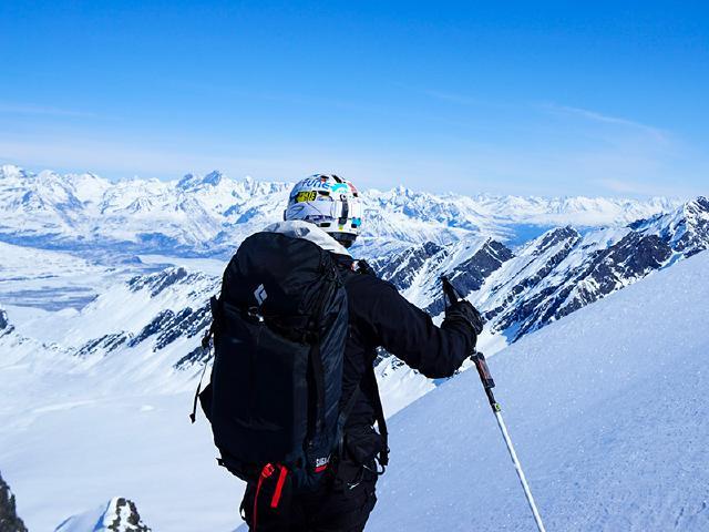 heli-skier at summit over looking glaciers in Alaska