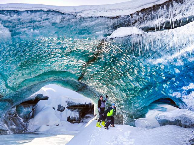 boyfriend and girlfriend couple exploring ice cave in Alaska as couple