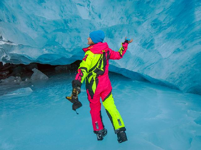 happy girl in snow suit dancing in ice cave surrounded by glacier
