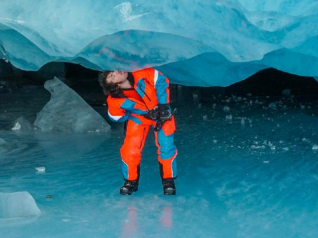 curious friend with snowsuit licking glacier ice in ice cave