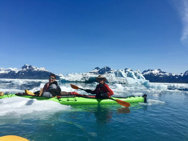 guide and software architect in two person kayak paddling through Columbia Glacier Bay through icebergs on sunny summer day