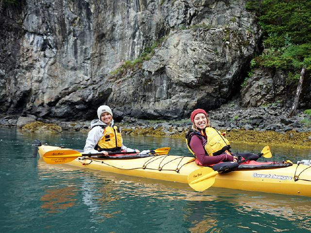 human resource leader and creative worker of artist paddling together on glacier bay near shoreline of wooded forest