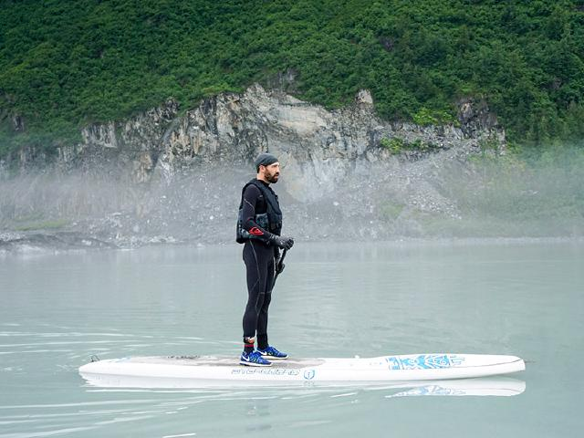 software engineer relaxed and disconnected while paddleboarding on lake in Alaska near Valdez