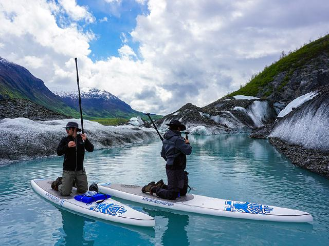 founders of startup company on paddleboards in glacier lake with icebergs and Sony Alpha mirrorless cameras