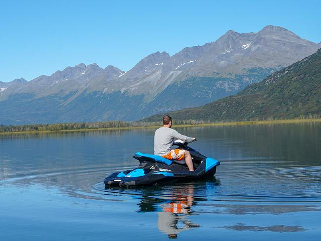 software engineer riding Seadoo slowly in morning after breakfast on calm and peaceful lake during summer