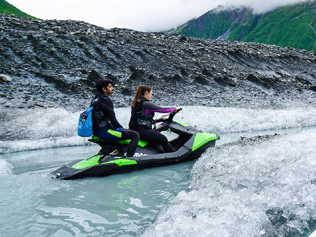 two tech workers on Seadoo driving up glacier stream on sunny day