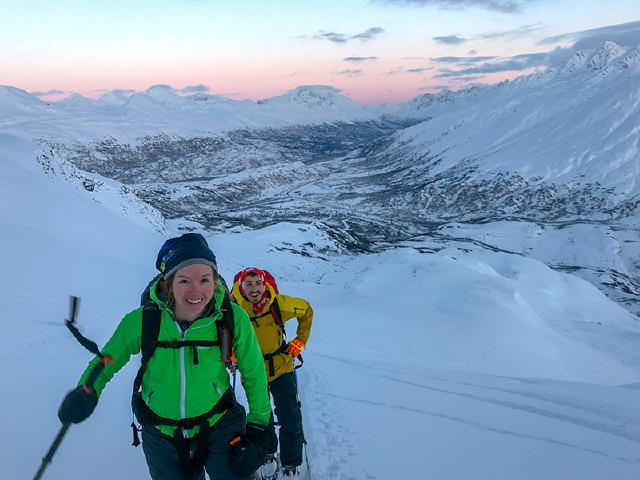 woman and man skinning up mountain in Thompson Pass during sunset for last run of the day
