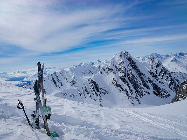 Armada skis and Black Diamond poles in snow at top of mountain in Alaska