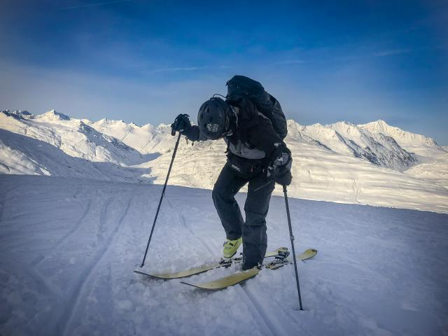 backcountry skier at top of mountain clipping Technica boots into Kingpin touring bindings