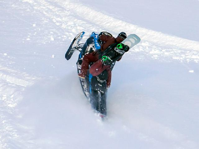 snowmobile ripping up breaking trail to backcountry snowboard
