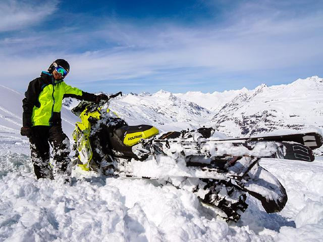 snowmachiner using Polaris with Armada skis and snowboard for lift up mountain in Thompson Pass