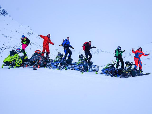 group of friends surfing snowmachines after lunch in Alaska