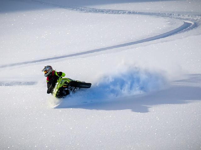 snowmobiler ripping on snow machine in fresh powder of Chugach Mountains