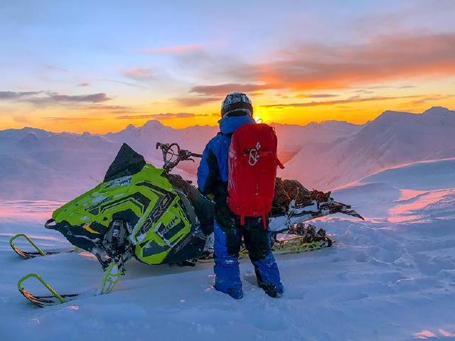 young professional with Black Diamond avalanche backpack and Polaris snowmachine watching best sunset at top of Loveland