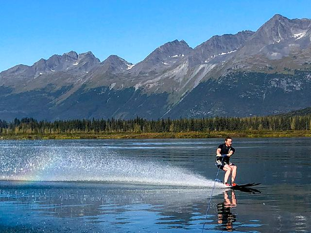 water skiing on smooth mountain lake carving in sunshine