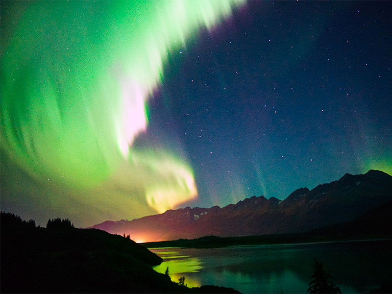 band of Northern Lights cross nightsky with reflection on water of lake