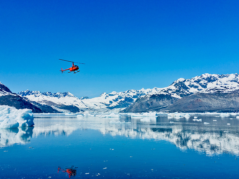 helicopter flying over Columbia Glacier bay with reflection on water on sunny bluebird day